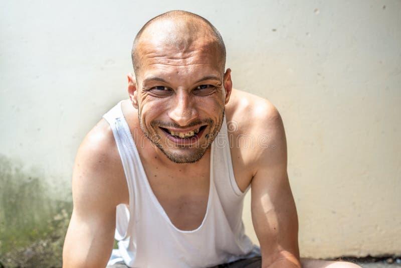 年轻皮包骨头的厌食秃头正面和愉快的微笑的无家可归的人坐都市街道在城市或镇在白色墙壁附近 库存照片