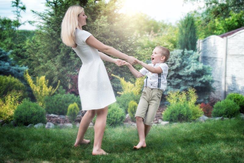 年轻盘旋母亲和的儿子握手 家庭度假在公园 免版税库存照片