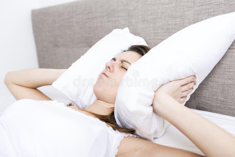 年轻睡觉的妇女在家佩带在白色的卧室 免版税图库摄影