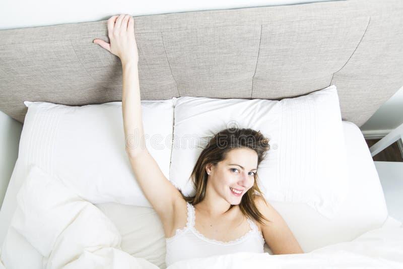 年轻睡觉的妇女在家佩带在白色的卧室 图库摄影