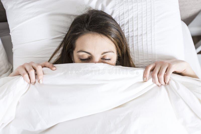年轻睡觉的妇女在家佩带在白色的卧室 库存照片