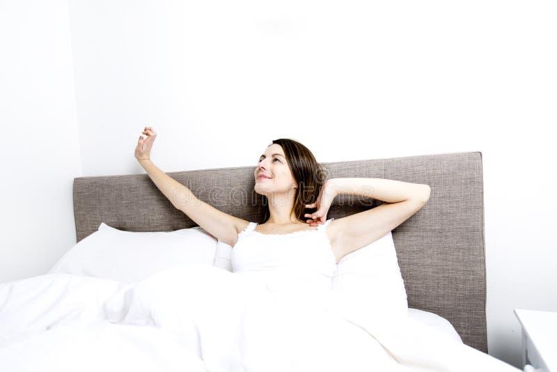 年轻睡觉的妇女在家佩带在白色的卧室 免版税库存照片