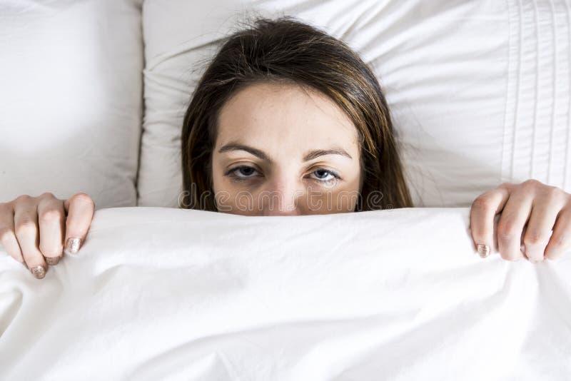 年轻睡觉的妇女在家佩带在白色的卧室 免版税库存图片