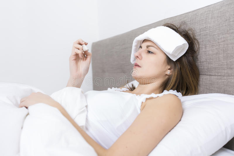 年轻睡觉的妇女在家佩带在白色的卧室 库存图片