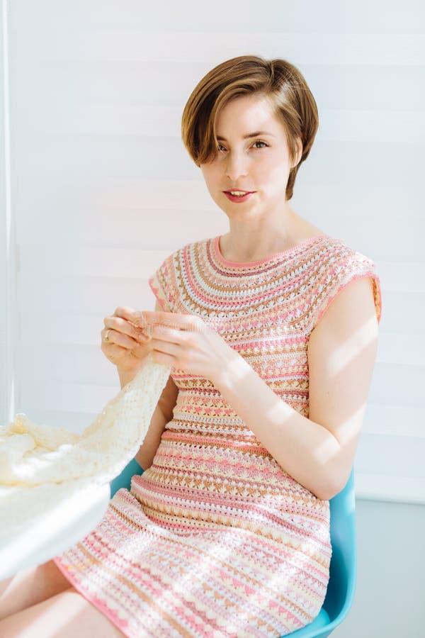 年轻短发妇女钩编编织物她的坐在厨房里的爱好的手工制造礼服在晴朗的早晨 事务钩编编织物手工制造在家 免版税图库摄影