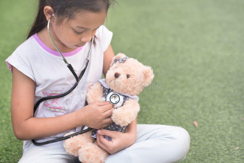 年轻矮小亚洲女孩使用假装是医生 女孩eaxamine她的与听诊器的玩具熊 库存照片