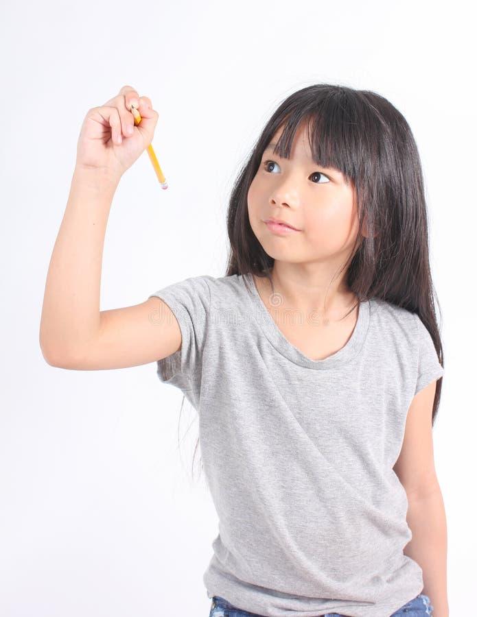 年轻矮小的亚洲女孩文字某事与黄色铅笔 库存图片