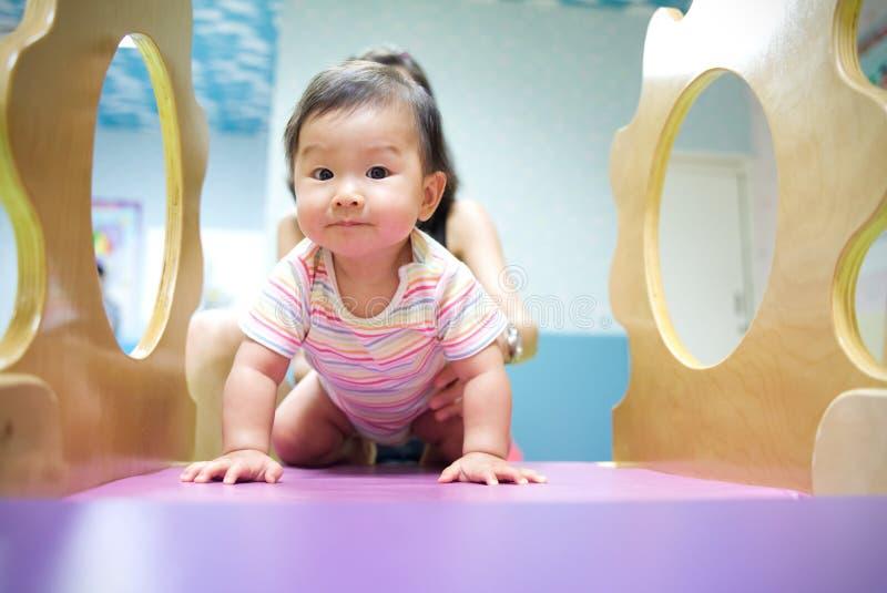年轻矮小的微笑的亚裔婴孩喜欢使用在孩子操场 母亲从她的藏品婴孩回到在滑子的戏剧与 库存图片