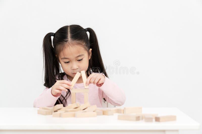 年轻矮小的逗人喜爱的亚裔女孩修建从木块建筑,木玩具,在书桌上的jenga房子的一个房子在绝尘室演播室 库存图片