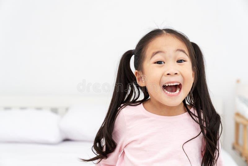 年轻矮小逗人喜爱亚洲女孩微笑和感到笑的乐趣激动,幸运和享用weeken在与关闭的绝尘室背景中 库存照片