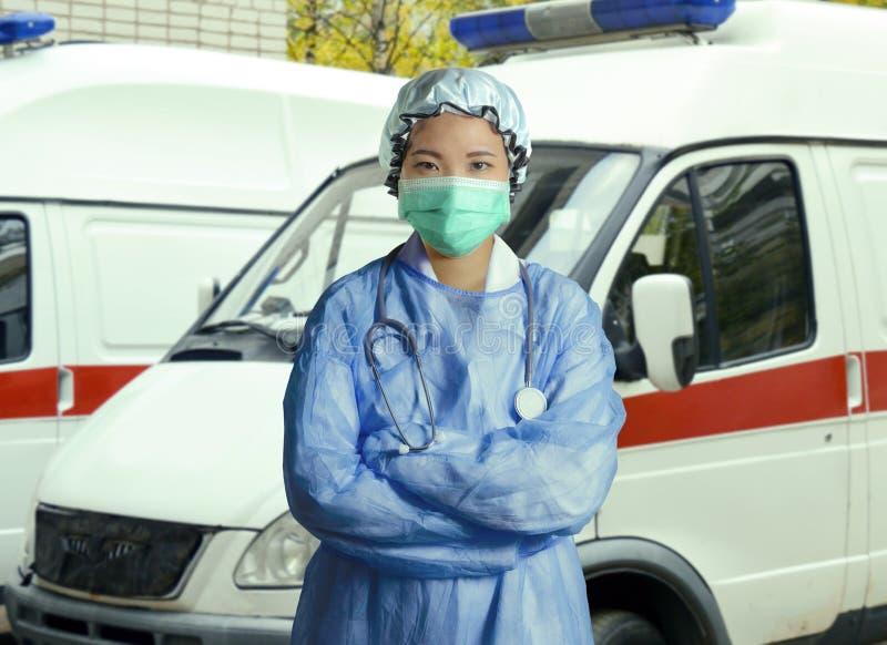 年轻确信和成功的亚裔韩国医学医生妇女在医院洗刷和摆在户外与ER救护车的面具 免版税库存照片