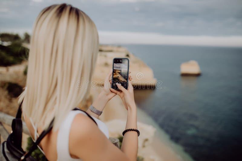 年轻秀丽妇女在葡萄牙拍在美好的海洋风景电话的照片与水和峭壁的 汽车城市概念都伯林映射小的旅行 免版税图库摄影