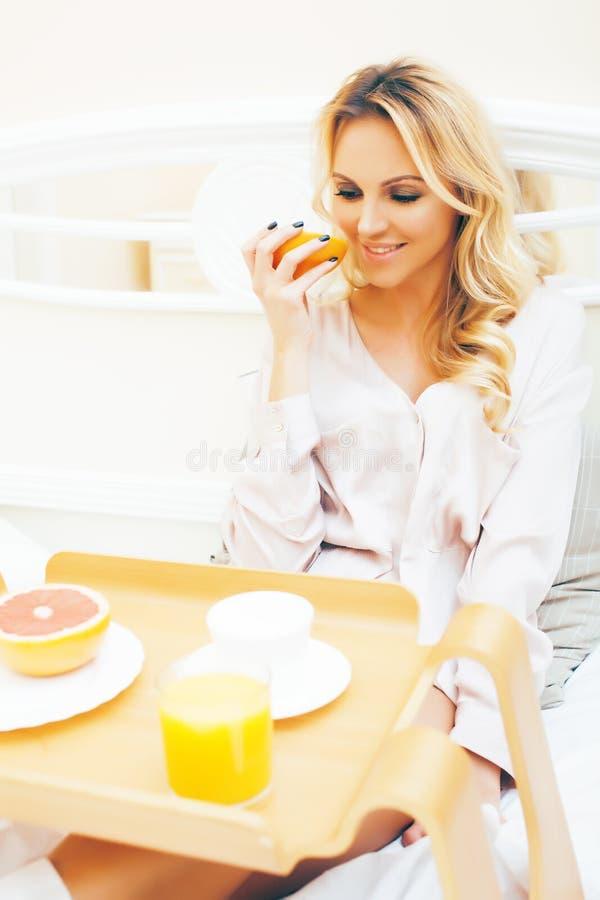 年轻秀丽白肤金发的妇女吃早餐在床早期的晴朗的早晨,公主房子内部室,健康生活方式 库存图片