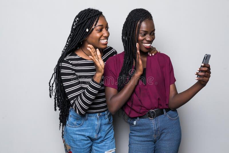 年轻秀丽非洲妇女在白色背景隔绝的电话做视频通话或selfie 免版税库存图片