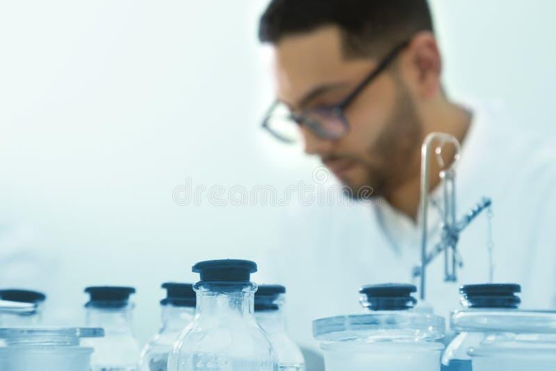 年轻科学家在一个化工实验室工作 所选的重点 免版税库存图片