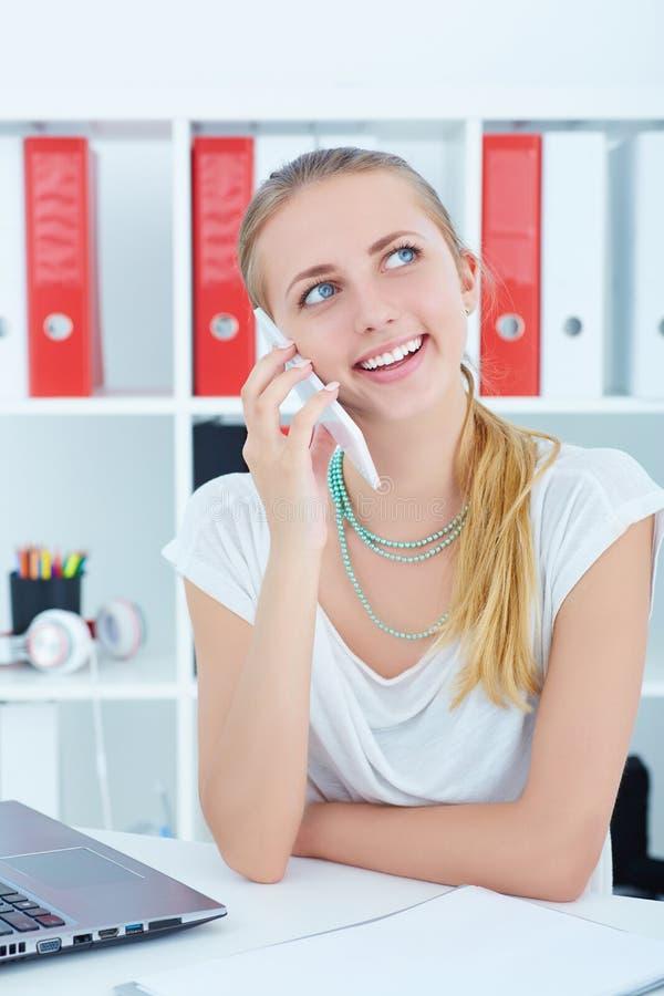 年轻秘书谈话在电话在办公室 库存图片