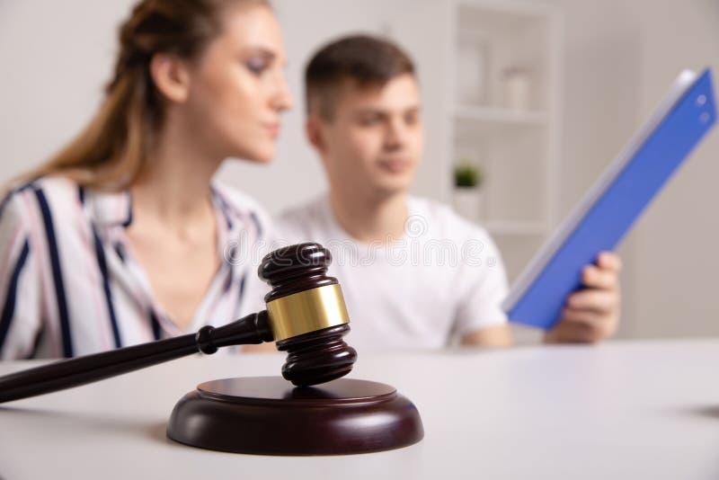 年轻租借人夫妇坐长沙发谈论租赁公寓与不动产房地产经纪商,在租赁协议的焦点和 免版税库存照片