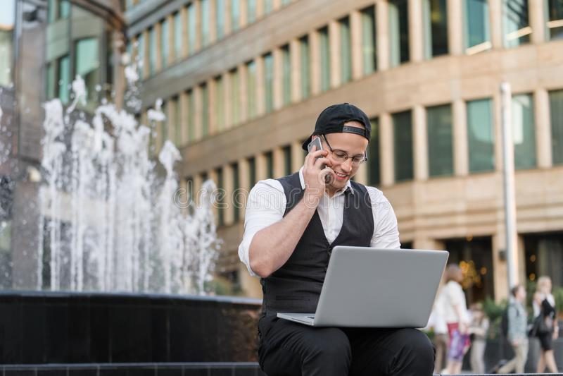 年轻程序员与膝上型计算机和电话一起使用户外 库存照片