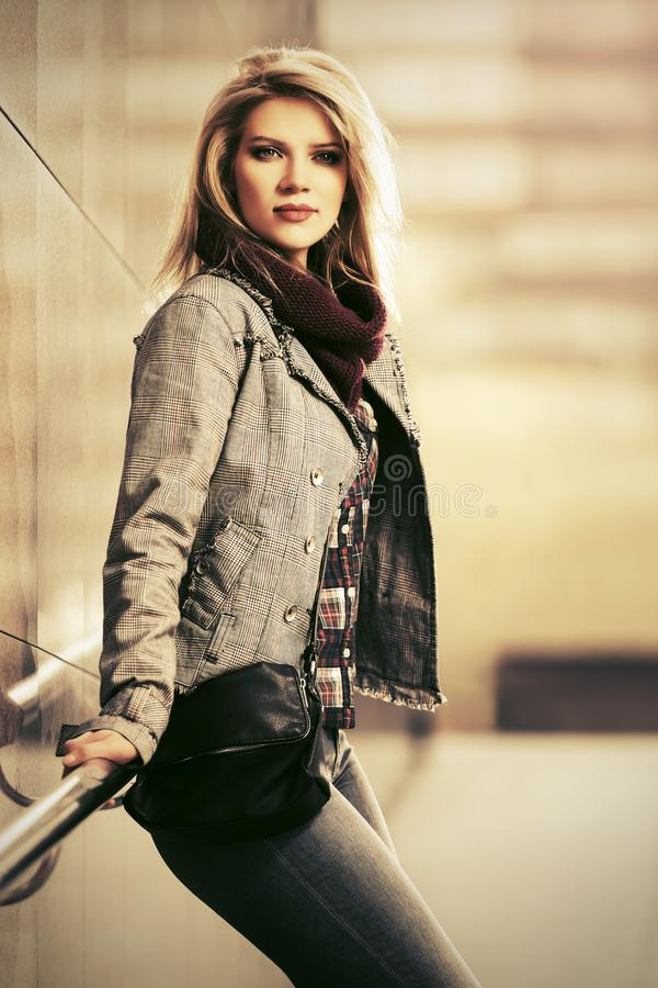 年轻穿在城市街道上的时尚白肤金发的妇女被检查的格子花呢披肩燃烧物 库存照片