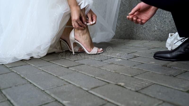 年轻穿着礼服凉鞋的丈夫帮助的新娘,事件的鞋子 免版税库存图片