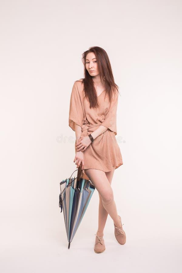 年轻站立与在白色背景的五颜六色的伞的brunnete亚裔妇女 免版税库存图片