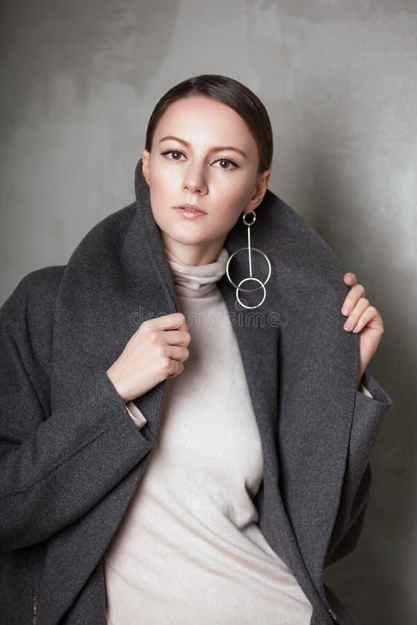 年轻端庄的妇女高档时尚画象在greyconcrete葡萄酒墙壁上的演播室 灰色外套 库存图片