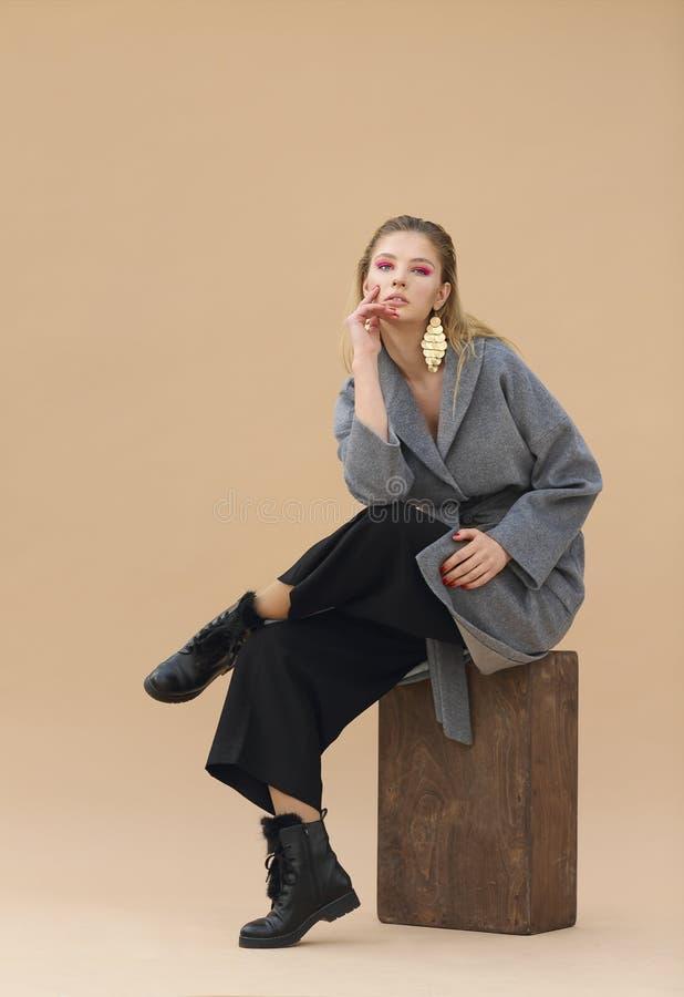 年轻端庄的妇女高档时尚画象灰色外套、黑色裤子、黑脚腕起动和金耳环的 库存图片