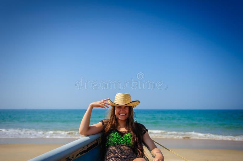 年轻笑的女孩画象有美丽的白色牙的在沙滩、绿松石海和明亮的天空蔚蓝背景  免版税图库摄影