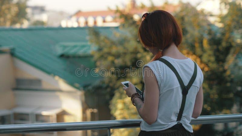 年轻红发妇女骑马自行车在城市 移动电话妇女 库存图片