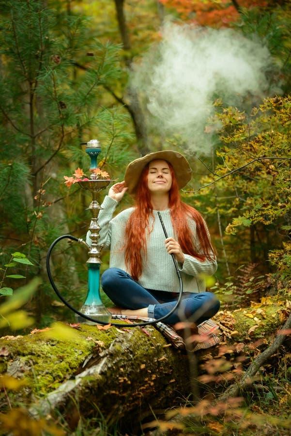 年轻红头发人妇女抽烟的水烟筒在森林里 库存照片