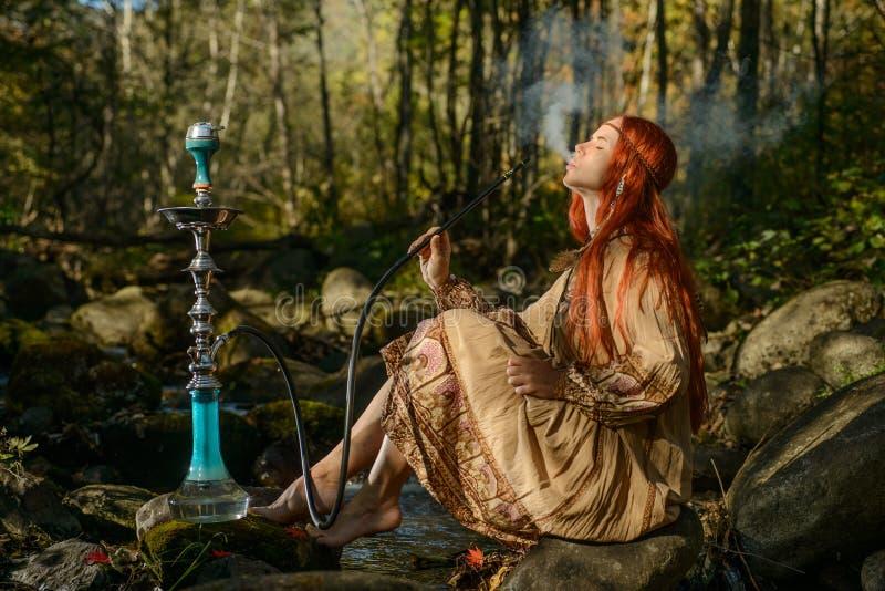 年轻红头发人嬉皮抽烟的水烟筒在森林里 库存图片
