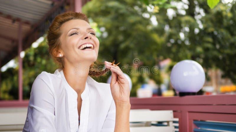 年轻红色头发和俏丽的妇女的图象有笑在咖啡馆的咖啡的 图库摄影