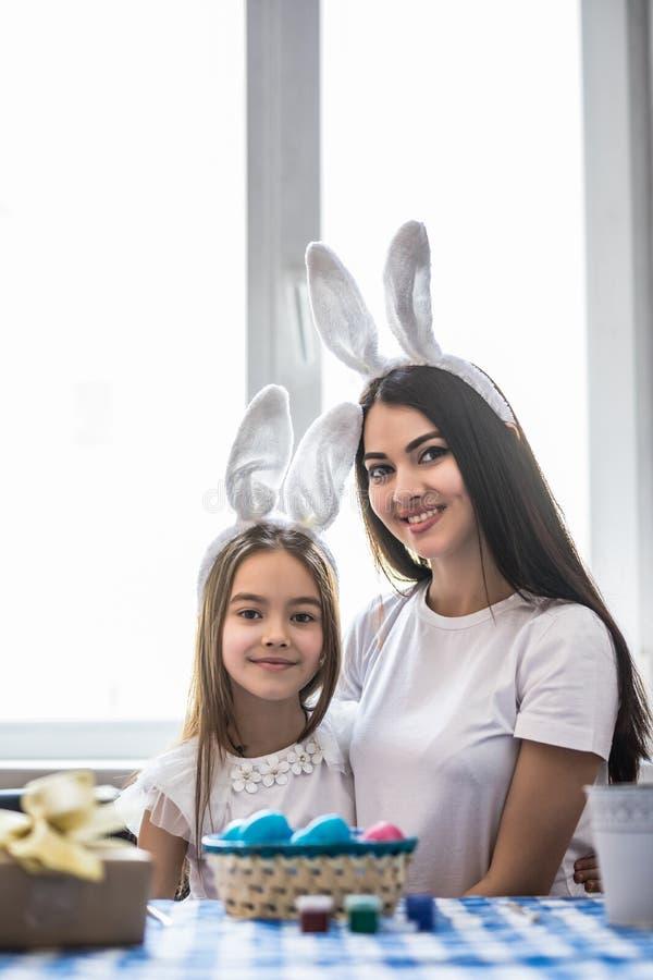 年轻绘复活节彩蛋的母亲和她的女儿 愉快的家庭为复活节做准备 逗人喜爱的小孩女孩佩带的兔宝宝耳朵o 免版税库存照片
