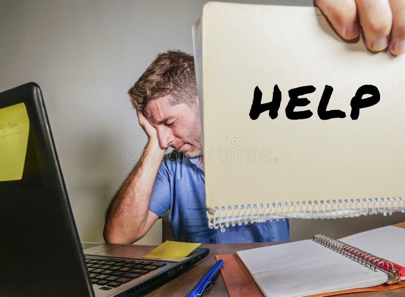 年轻绝望和被注重的商人感觉淹没了工作与便携式计算机在办公桌哀伤的痛苦重音aski 免版税库存照片