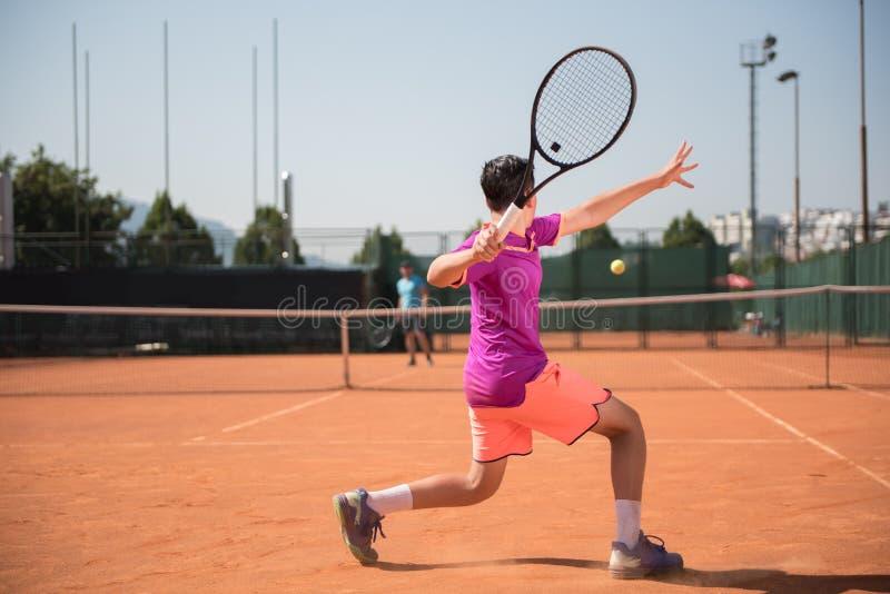 年轻网球员为演奏正手击球做准备 免版税库存照片