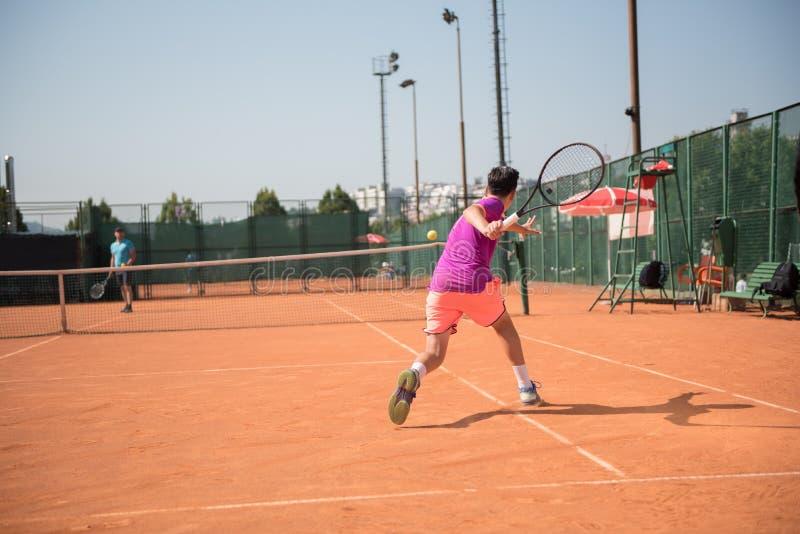 年轻网球员为演奏正手击球做准备 库存图片