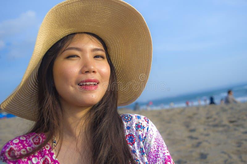年轻美丽和愉快的亚裔中国旅游妇女生活方式画象的关闭夏天帽子微笑的快乐对热带是 免版税库存照片