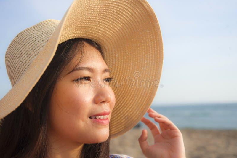 年轻美丽和愉快的亚裔中国旅游妇女生活方式画象的关闭夏天帽子微笑的快乐对热带是 图库摄影