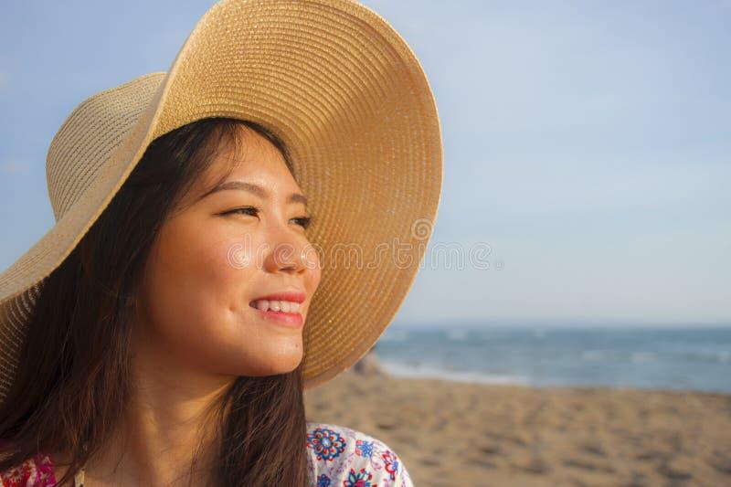 年轻美丽和愉快的亚裔中国旅游妇女生活方式画象的关闭夏天帽子微笑的快乐对热带是 库存图片