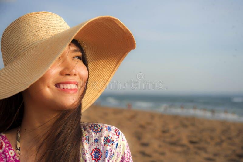 年轻美丽和愉快的亚裔中国旅游妇女生活方式画象的关闭夏天帽子微笑的快乐对热带是 库存照片