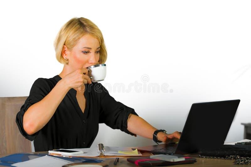年轻美丽和愉快的妇女公司业务画象有金发饮用的咖啡工作的放松了在办公室膝上型计算机c 免版税库存照片