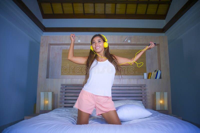 年轻美丽和愉快的学生妇女亚洲拉丁种族与耳机在跳舞的床上混合了听到音乐唱歌和 库存照片