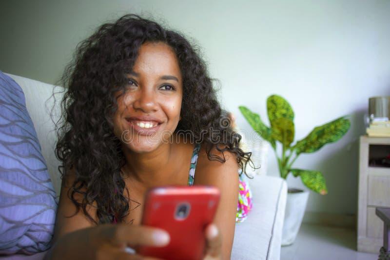 年轻美丽和愉快的混杂的种族在家说谎长沙发使用手机应用程序的白种人和黑人美国黑人的妇女 库存图片