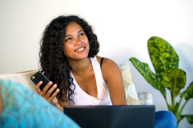 年轻美丽和愉快的混杂的种族在家说谎长沙发使用手机的白种人和黑人非裔美国人的妇女和 库存图片