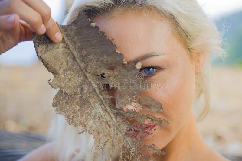 年轻美丽和愉快的白肤金发的女孩户外浪漫画象有使用与秋天树叶子覆盖物的华美的蓝眼睛的 库存图片