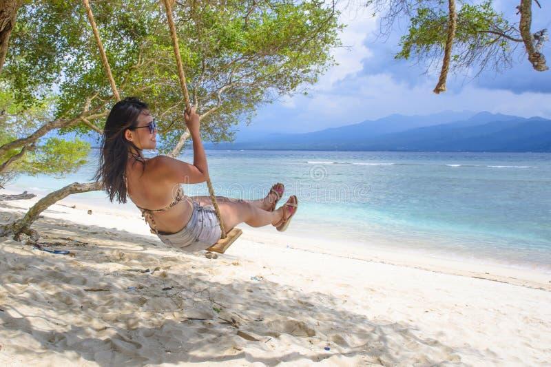 年轻美丽的中国亚裔女孩获得在海滩任意享受愉快的感觉的树摇摆的乐趣在暑假热带旅行 库存照片