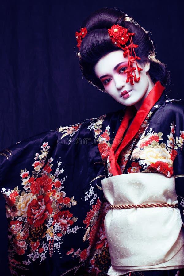年轻美丽的亚洲妇女` s画象,和服的艺妓在blac 免版税库存照片
