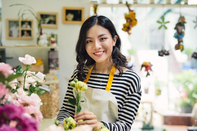 年轻美丽的亚裔女孩卖花人照料花在wor 库存照片