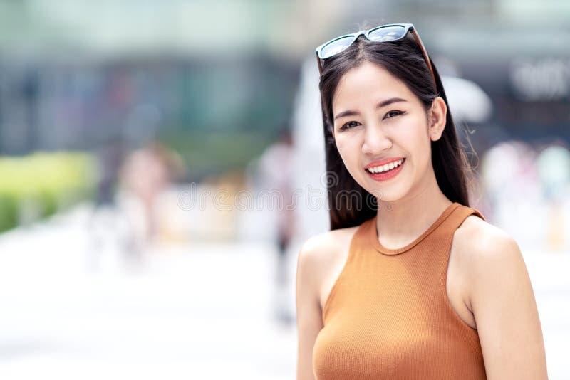 年轻美丽的亚裔妇女、博客作者、vlogger或者时髦的时尚画象微笑和看佩带肩膀的照相机 免版税库存图片
