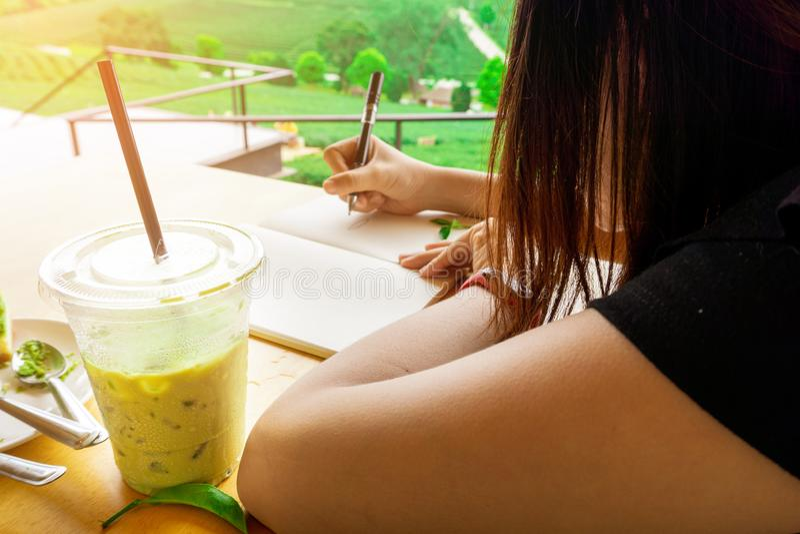 年轻美丽的亚裔妇女是工作,画或者写在与塑料杯子的纸被冰的绿茶和美好的绿色自然 库存图片